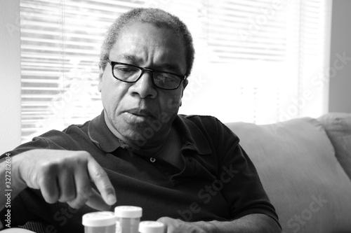 Stampa su Tela Male senior taking his medication at home.