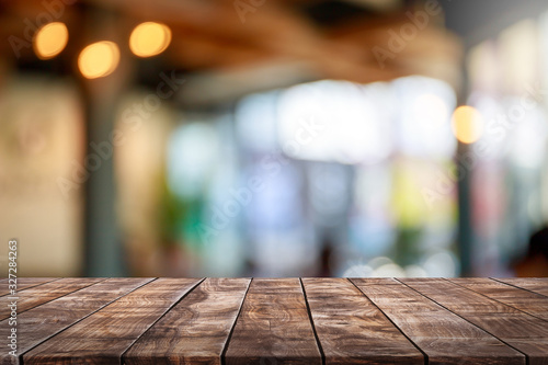 Fototapeta Empty wood table top and blur glass window interior restaurant banner mock up abstract background - can used for display or montage your products. obraz