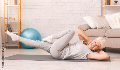 Fotografia Sporty senior woman doing abs exercise on floor at home