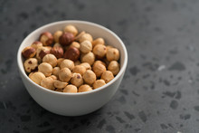 Roasted Hazelnuts In White Bowl On Concrete Background