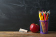 Apple, pencils and chalk on table in classroom