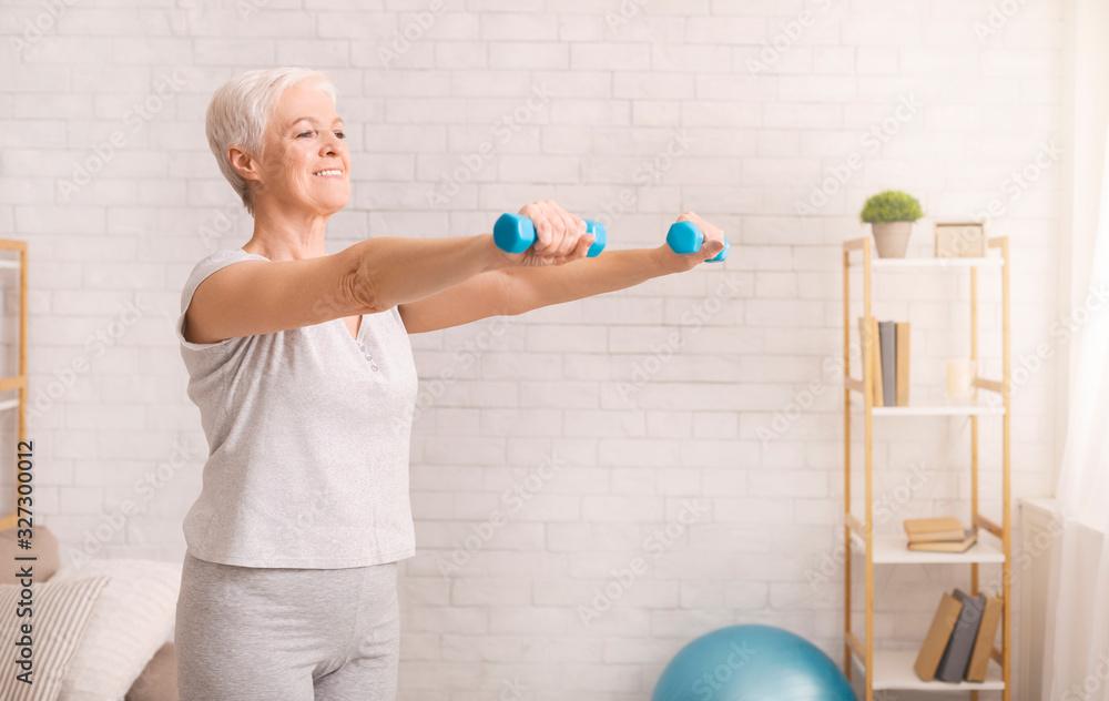 Fototapeta Senior woman exercising with dumbbells at home