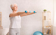 Senior woman exercising with dumbbells at home