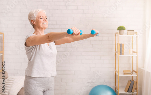 Obraz Senior woman exercising with dumbbells at home - fototapety do salonu