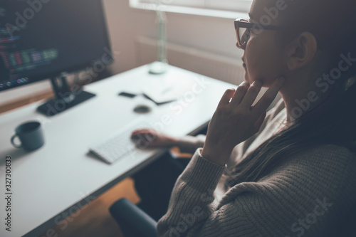 Side view of young woman working on computer from her home office