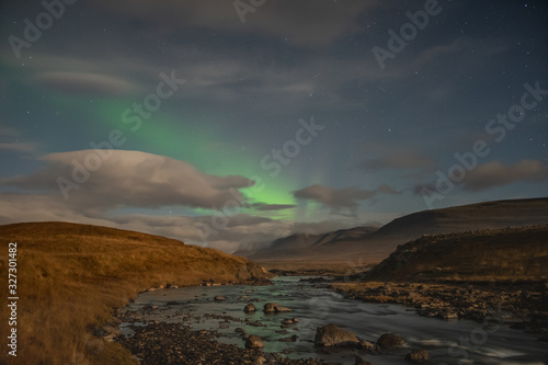 Valokuva Aurora Borealis in Iceland northern lights shining green and reflecting in river