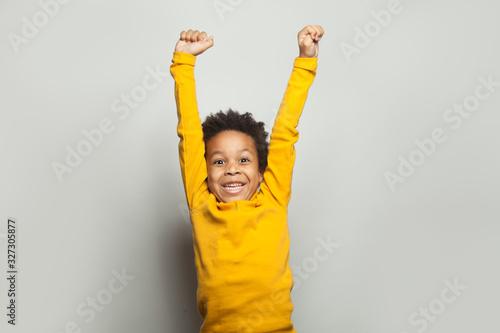 Obraz Little black child win-win! Kid boy having fun on white background - fototapety do salonu