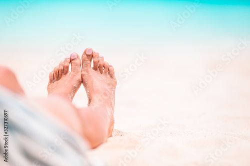 Fotografie, Tablou Woman's feet on the white sand beach in shallow water