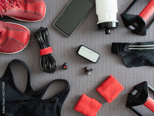 Obraz top view sport wear concept with Gym Outfit, running shoes, smartphone, true wireless earbuds and sport run accessories on on yoga mat background. - fototapety do salonu