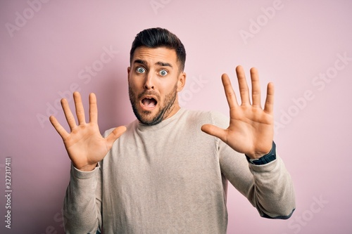 Young handsome man wearing casual sweater standing over isolated pink background afraid and terrified with fear expression stop gesture with hands, shouting in shock Canvas Print