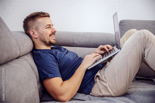 Obraz Side view of attractive bearded smiling man lying on sofa and using laptop for internet surfing. - fototapety do salonu