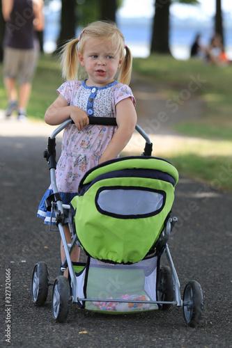 Photo Kleines Mädchen mit Puppenwagen