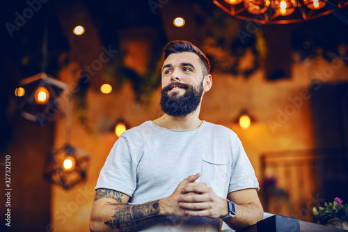 Foto Low angle view of attractive smiling caucasian bearded tattooed hipster leaning on table in cafe and looking away