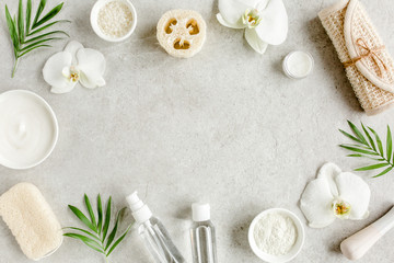Fototapeta na wymiar Spa treatment concept. Natural/Organic spa cosmetics products, sea salt, massage brush, tropic palm leaves on gray marble table from above. Spa background with a space for a text, flat lay, top view