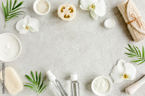 Fototapeta Spa treatment concept. Natural/Organic spa cosmetics products, sea salt, massage brush, tropic palm leaves on gray marble table from above. Spa background with a space for a text, flat lay, top view
