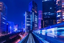 Japan. The Train Goes Through Tokyo In The Evening. The Train Rushes Along The Tracks Along The Skyscrapers. Railway Traffic In The Business Part Of Tokyo. Evening Life Of The Japanese Capital.