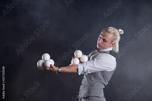 Fototapeta Juggler wearing a suit like a businessman with white balls. concept of success and management obraz