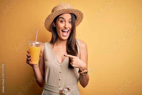 Fotomural Young beautiful woman on vacation wearing summer hat drinking healthy orange jui
