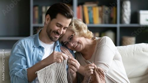 Fototapeta Smiling mature mom and adult son knitting together obraz