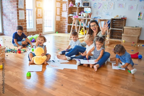 Obraz Beautiful teacher and group of toddlers sitting on the floor drawing using paper and pencil around lots of toys at kindergarten - fototapety do salonu
