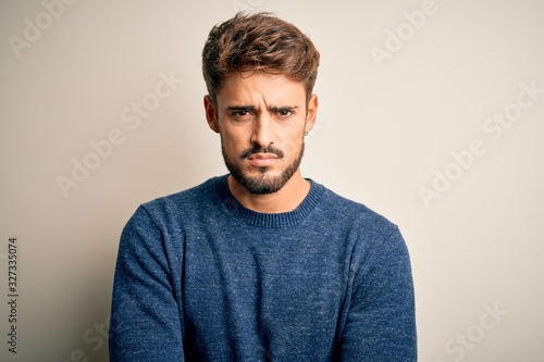 Obraz Young handsome man with beard wearing casual sweater standing over white background skeptic and nervous, disapproving expression on face with crossed arms. Negative person. - fototapety do salonu