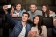 Young friends with mobile phone taking selfie in cinema