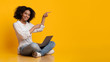 canvas print picture - Cheerful Afro Girl Sitting On Floor With Laptop And Pointing Aside