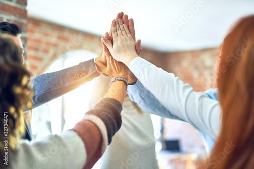 Obraz Group of business workers standing with hands together highing five at the office - fototapety do salonu