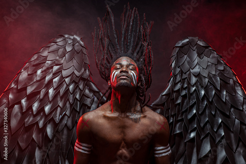 Valokuva portrait of reckless dark angel with strong muscles, having athletic body, afric