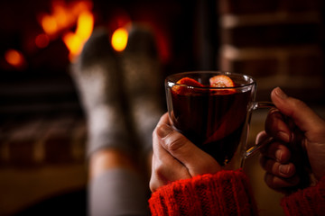 Woman with tasty mulled wine near burning fireplace indoors, closeup