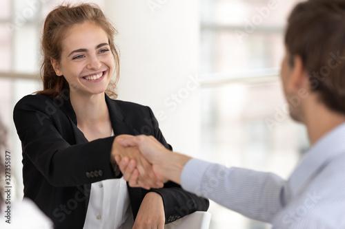 Photo Smiling attractive businesswoman handshaking businessman at meeting negotiation