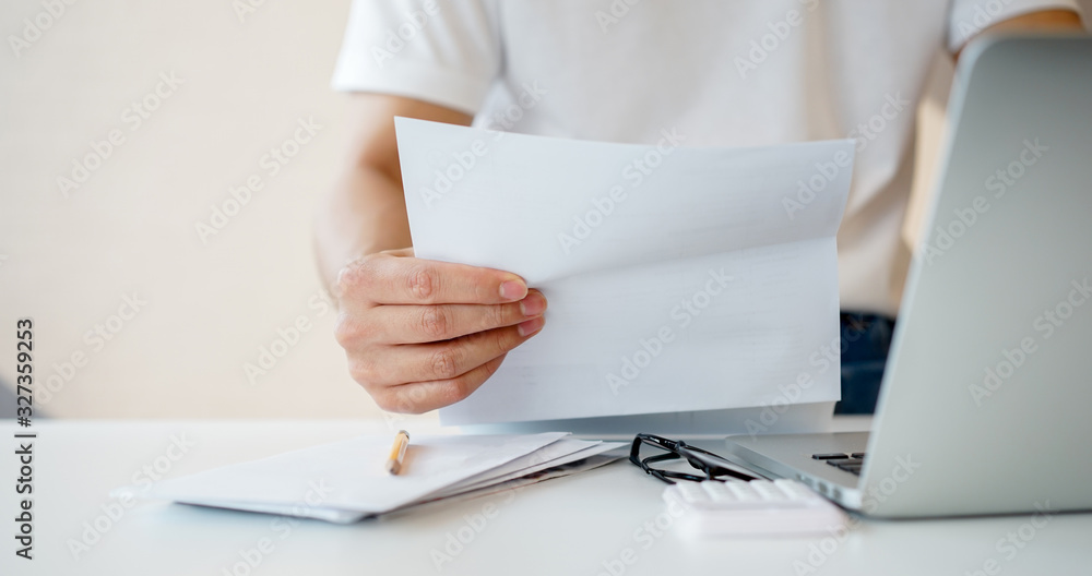 Fototapeta close up man hand holding invoice paper form mail to reading and check list of spending of the month and planing to manage money for financial and life concept