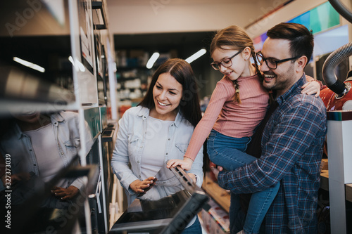 Tablou Canvas Happy family buying oven in store.