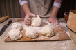 A woman kneads the dough. Plywood cutting board, wooden flour sieve and wooden rolling pin - tools for making dough.
