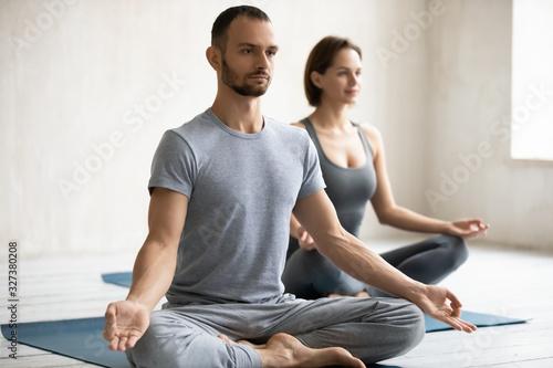 Fototapeta People meditating sitting on mats, focus on male instructor obraz
