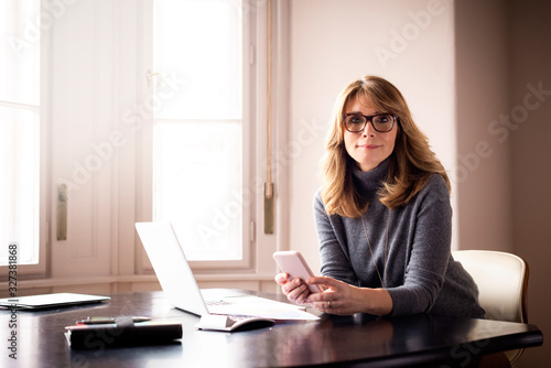 Smiling businesswoman using her mobile phone and text messaging while working fr Canvas Print