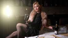 1920s Retro Style. Beautiful Young Woman In A Dress Sits On A Table And Smokes In A Luxury Interior, Drinks Champagne In A Beautiful Light. The Photo Shows Soft Noise For A Vintage Style. Color Photo