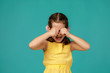 upset little child girl is crying on blue background. girl wiping tears