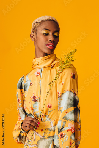 Portrait of  a beautiful young woman holding yellow flower, with trendy fresh makeup of orange lips and yellow eyeshadow Wall mural