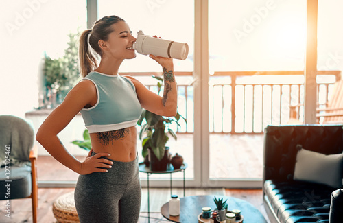 Athletic woman in sportswear drinking a protein shake or a bottle of water at home in the living room Obraz na płótnie
