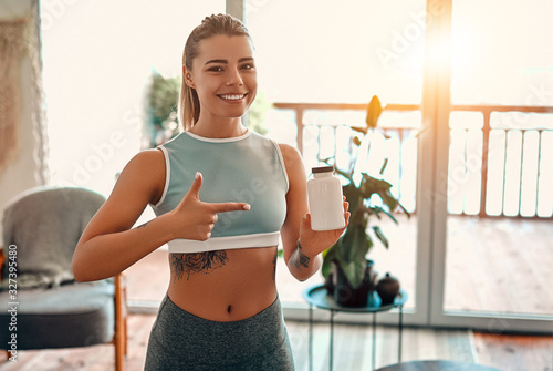 Fotografía Athletic woman in sportswear holds a jar of protein in her hand and shows a finger gesture at home in the living room