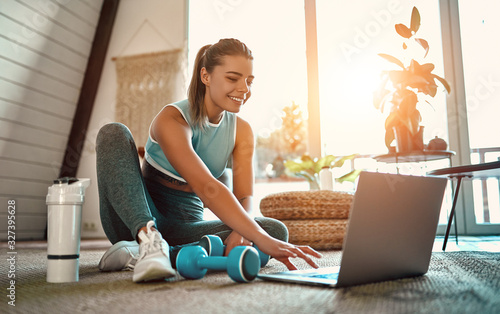Fototapeta A sporty woman in sportswear is sitting on the floor with dumbbells and a protein shake or a bottle of water and is using a laptop at home in the living room. Sport and recreation concept. obraz