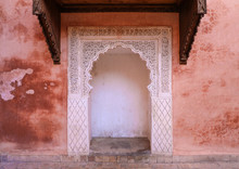 Delicate Carved White Archway Against Pink Building