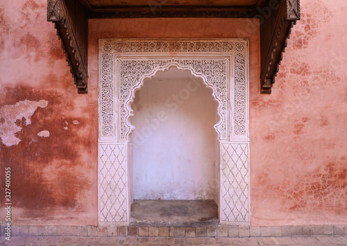 Foto Delicate carved white archway against pink building