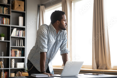 Foto Thoughtful african american businessman leaning on table, looking away