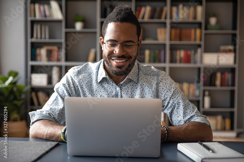 Fototapety, obrazy: Young smiling african american businessman looking at laptop screen.