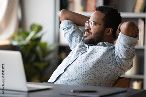 Peaceful carefree young african american guy relaxing on comfortable chair Wallpaper Mural
