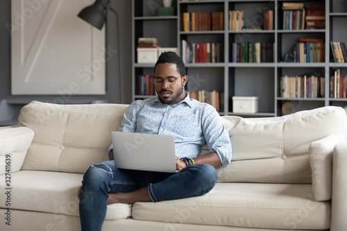 Focused young african american businessman working remotely online Wallpaper Mural