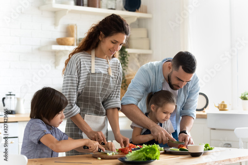 Young family with little kids cooking at home together - 327423655