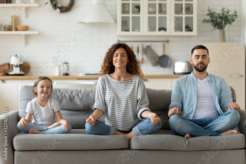 Fotomural Young family with little daughter practice yoga together
